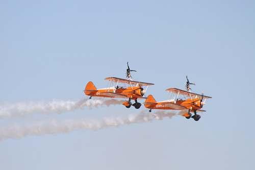 biplane photo of two orange flying biplanes airplane