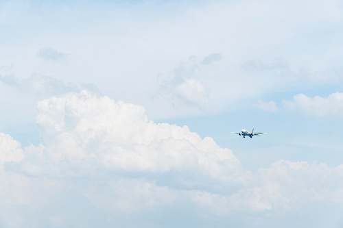 blue photo of white commercial airplane flying in sky under white clouds flying