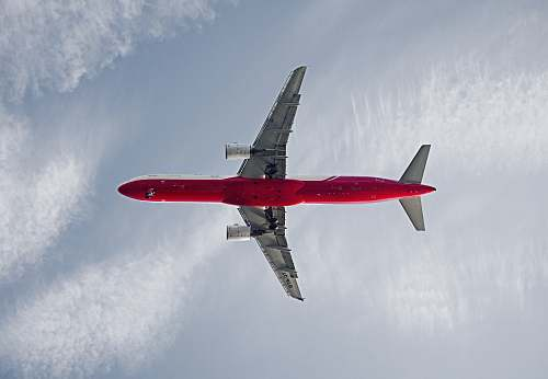 transportation red and white passenger airplane on the sky during daytime aircraft