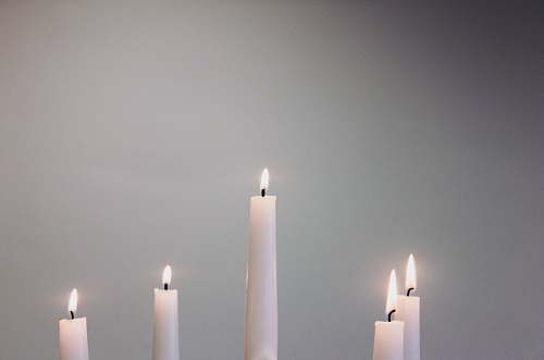 grey five lit white taper candles flame