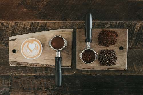 nature coffee beans beside coffee powder on brown wooden board countryside