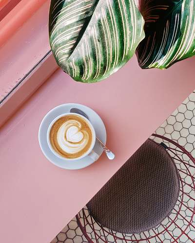 pink cup of coffee on saucer with teaspoon on pink tabletop london