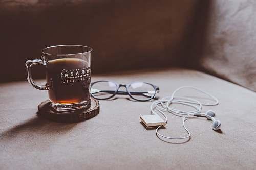 coffee clear Brain printed glass mug on brown wood slab coaster beside black framed eyeglasses and white earphones coffee cup