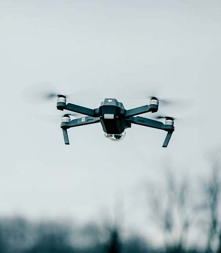 fly selective focus photography of flying quadcopter equipment