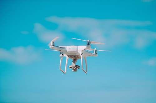 fly white quadcopter flying during daytime flight