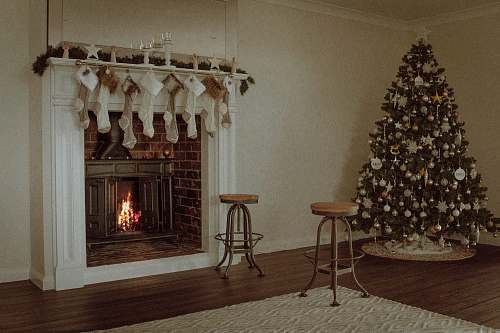 photo hearth Christmas tree near two barstools at fireplace christmas tree free for commercial use images