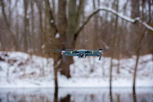 photo camera flying black drone during winter winter free for commercial use images