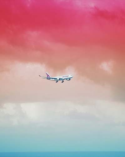 color Qatar Airlines airplane flying under red cloud formation maldives