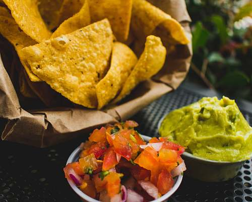 nachos fried crackers with red tomatoes and green sauce bowl