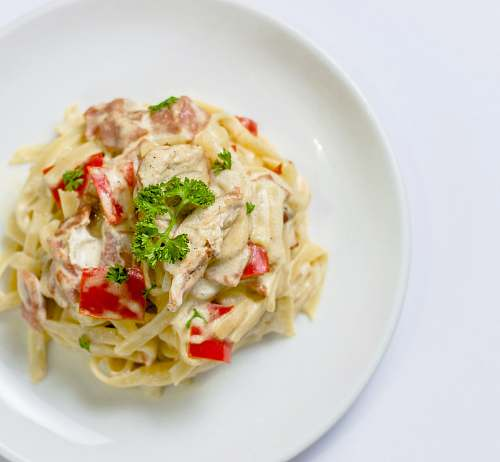 meal plate of white pasta with red bell pepper dish
