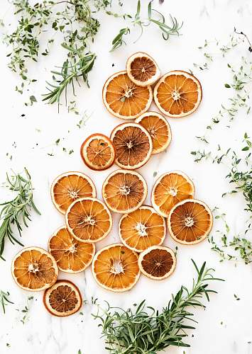 fruit sliced lemons surrounded by green herbs orange