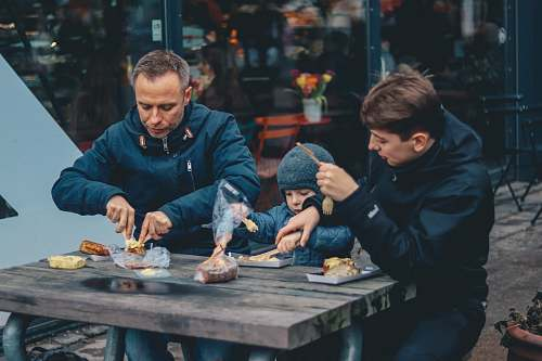 photo person two man and boy sitting in front of table eating human free for commercial use images