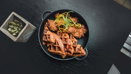 pasta waffle near fried food in black pot near green succulent plant noodle