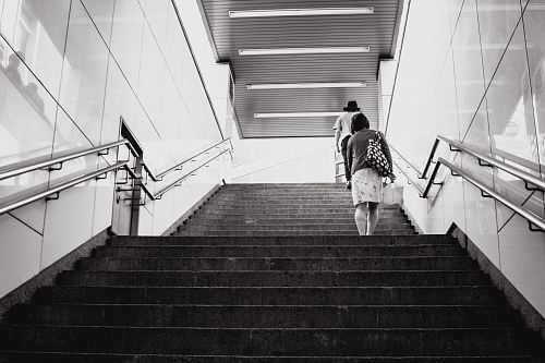 grayscale photography of woman walking on stair