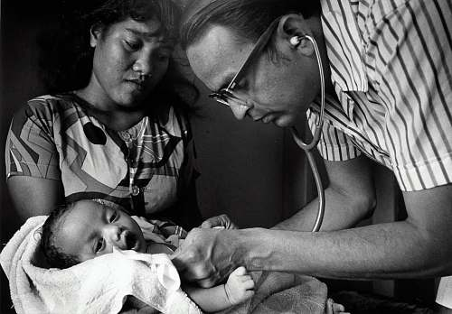 person doctor checking baby black-and-white