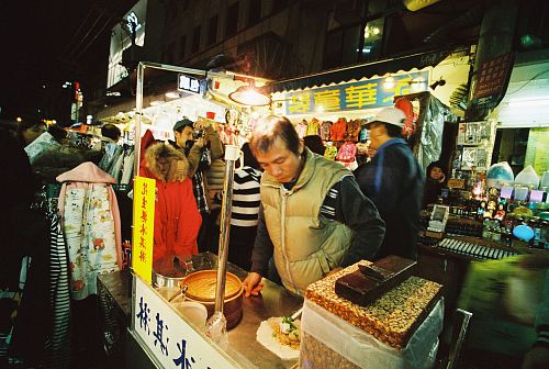 man preparing food on food stall with light bulb