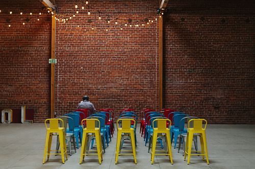 photo man sitting on red chair in front of brown concrete brick wall free for commercial use images