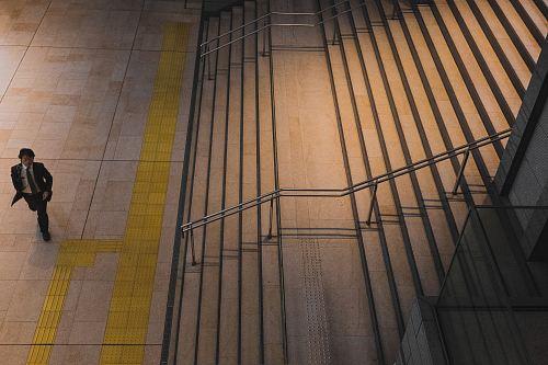 man walking in front of grey steel stair railing