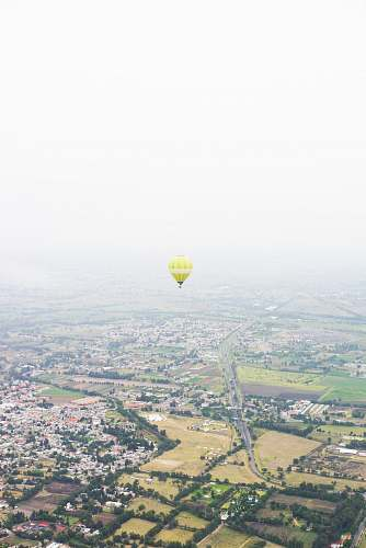 sky photo of yellow hot air balloon floating above houses hot air balloon