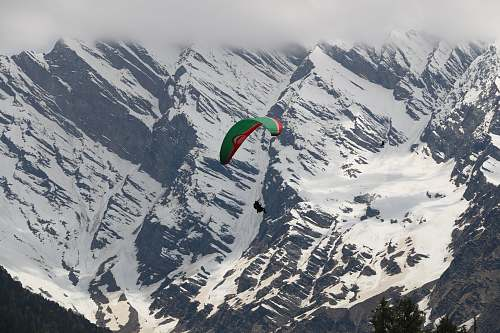 snow person paragliding above snowy mountains during daytime peak
