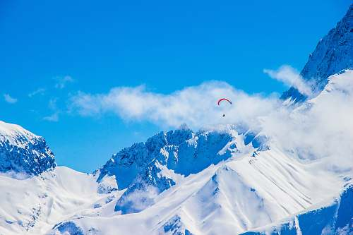 photo nature photo of person with parachute above snowy mountain snow free for commercial use images