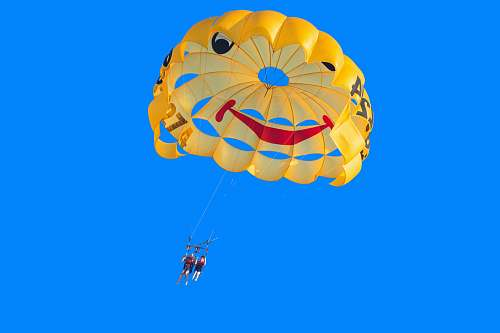 photo adventure two person in yellow, red, and black parachute under blue sky during daytime leisure activities free for commercial use images