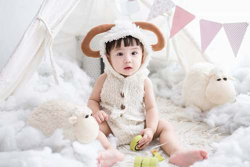 photo person baby sitting beside white sheep plush toy human free for commercial use images
