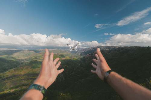 human person pointing both hands on white drone during daytime people