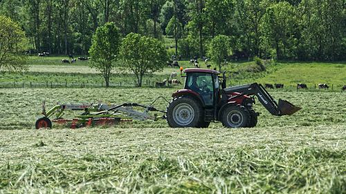 photo red tractor with farming attachment on field during daytime free for commercial use images