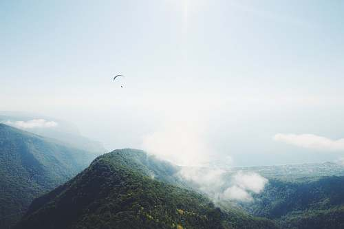 mountain mountain covered by clouds paraglide