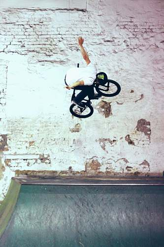 bike man riding black BMX bike doing bike tricks fly