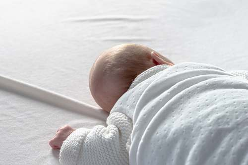 human baby lying on white surface person
