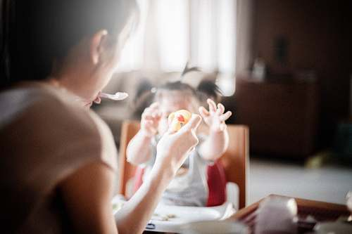 child selective focus photography of woman feeding baby mother
