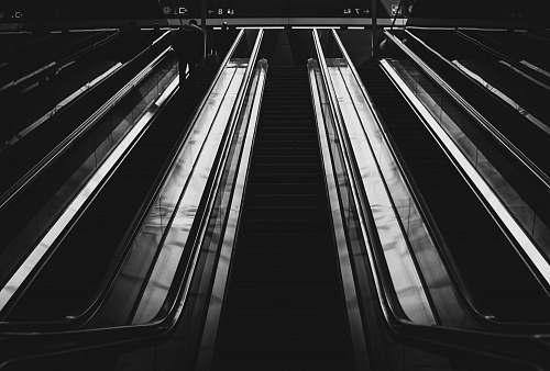 banister grayscale photography of escalators handrail