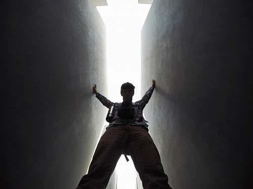 person low-angle photo of man standing between walls lighting