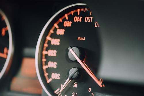 dashboard closeup photo of black analog speedometer closeup