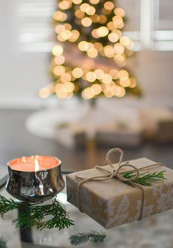 photo holiday brown gift box beside stainless steel votive candle gift free for commercial use images