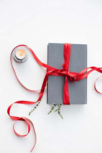 gift gray book wrapped with red ribbon beside teallight candle red