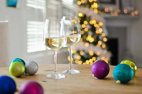 photo glass two clear footed wineglasses filled with yellow liquid near assorted-color ball ornaments goblet free for commercial use images