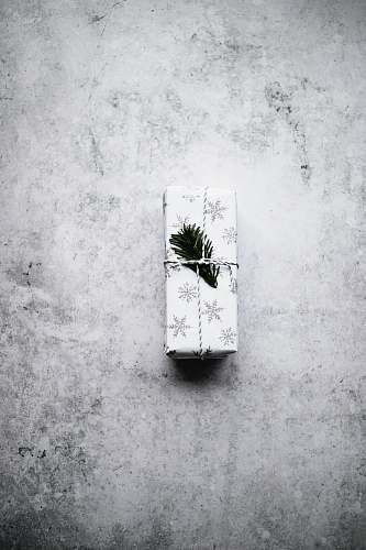 photo grey white and black snowflake print gift box on gray surface wall free for commercial use images