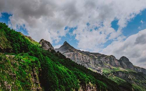 alpes green covered mountains under blue and white sky france