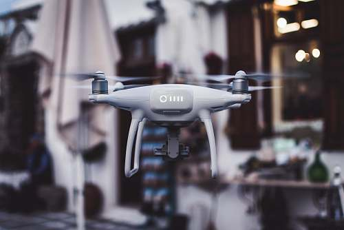 street tilt shift lens photography of gray Phantom drone fly