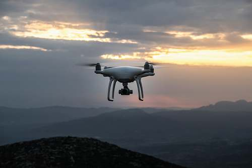 photo greece white DJI quadcopter drone flying in mid-air sunset free for commercial use images