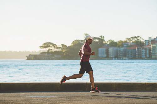 photo person man running near sea during daytime sports free for commercial use images