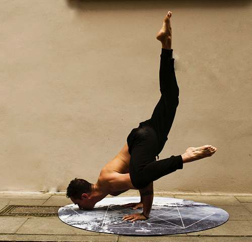photo yoga man doing stunt near brown wall exercise free for commercial use images