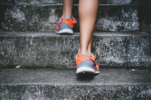 people person wearing orange and gray Nike shoes walking on gray concrete stairs sport