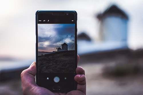 mykonos man using phone taking photo of the house phone