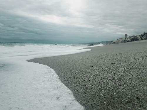 sea beach under cloudy sky beach