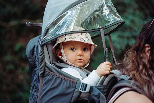 person baby inside black backpack carrier people