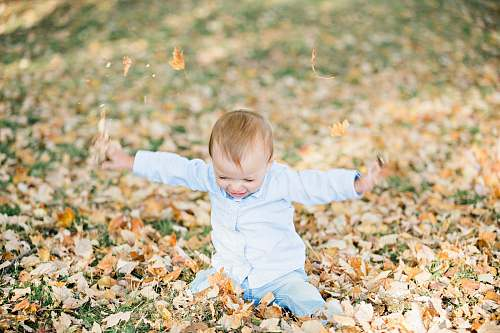 photo person baby on ground with dried leaves leaf free for commercial use images